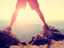 Étape au-dessus de jungle Sun entre les jambes Faites les jambes nues en pantalon et sandales de trekking faire l'étape sur la ro Photo stock
