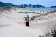 Étape de dame âgée sur le sandhill désolé. QUY NHON, VIETNAM 18 JUIN Photographie stock