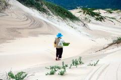 Étape de dame âgée sur le sandhill désolé. QUY NHON, VIETNAM 18 JUIN Images stock