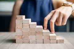 Étape de doigt de femme d'affaires sur le bâtiment en bois de bloc images libres de droits