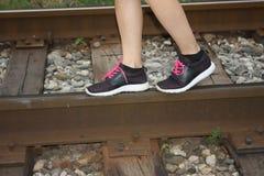 Étape de pied d'espadrilles de sport le chemin de fer de rail Image stock