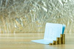 Étape de pile de pièce de monnaie avec le carnet ou de livre de comptes sur le worki en bois photo libre de droits