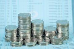 Étape de pile de pièce de monnaie avec le carnet ou de livre de comptes sur le worki en bois photographie stock