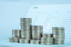 Étape de pile de pièce de monnaie avec le carnet ou de livre de comptes sur le worki en bois photos stock