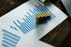 Étape des piles de pièces de monnaie avec l'ordinateur portable de carnet et financier Photo stock