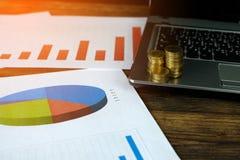 Étape des piles de pièces de monnaie avec l'ordinateur portable de carnet et financier Images libres de droits