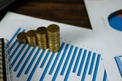 Étape des piles de pièces de monnaie avec l'ordinateur portable de carnet et financier Photos stock