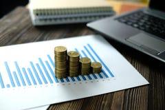 Étape des piles de pièces de monnaie avec l'ordinateur portable de carnet et financier Image libre de droits