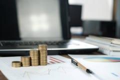 Étape des piles de pièces de monnaie avec l'ordinateur portable de carnet et financier Image stock