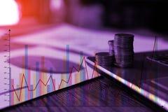 Étape des piles de pièces de monnaie avec l'ordinateur portable de carnet et financier Photo libre de droits