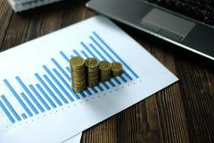 Étape des piles de pièces de monnaie avec l'ordinateur portable de carnet et financier Photographie stock libre de droits