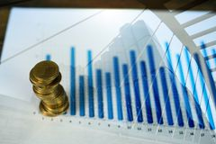 Étape des piles de pièces de monnaie avec l'ordinateur portable de carnet et financier Photographie stock