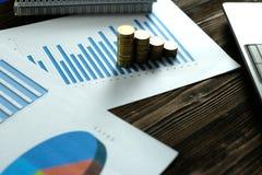 Étape des piles de pièces de monnaie avec l'ordinateur portable de carnet et financier Photos libres de droits