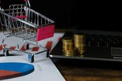Étape des piles de pièces de monnaie avec l'ordinateur portable de chariot et de carnet a Photo stock