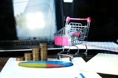 Étape des piles de pièces de monnaie avec l'ordinateur portable de chariot et de carnet a Photo libre de droits