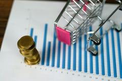 Étape des piles de pièces de monnaie avec l'ordinateur portable de chariot et de carnet a Images stock