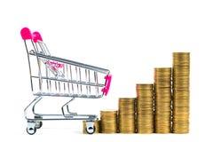 Étape des piles des pièces de monnaie et du caddie ou du chariot à supermarché Photographie stock
