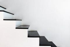 Étape noire d'escaliers blancs de mur Photographie stock
