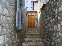 Étapes de murs en pierre et entrée de cour avec la porte en bois Photographie stock libre de droits