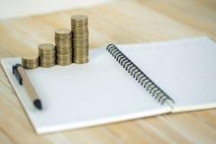 Étapes de pile de pièces de monnaie avec le papier de carnet sur la table de fonctionnement en bois Image stock