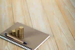 Étapes de pile de pièces de monnaie avec le papier de carnet sur la table de fonctionnement en bois Photo libre de droits