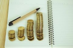 Étapes de pile de pièces de monnaie avec le papier de carnet sur la table de fonctionnement en bois Images stock