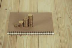 Étapes de pile de pièces de monnaie avec le papier de carnet sur la table de fonctionnement en bois Photos stock