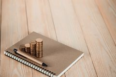 Étapes de pile de pièces de monnaie avec le papier de carnet sur la table de fonctionnement en bois Photographie stock