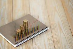 Étapes de pile de pièces de monnaie avec le papier de carnet sur la table de fonctionnement en bois Images libres de droits