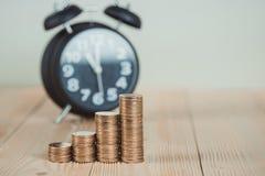 Étapes de pile de pièces de monnaie avec le réveil de vintage sur le travail en bois Photo stock