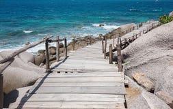 Étapes en bois légères entourées par la mer et les grandes pierres image stock