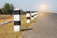 Étapes importantes, étapes importantes noires et blanches avec le bord de la route d'herbe verte, Photo stock