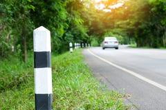 Étapes importantes noires et blanches avec le bord de la route d'herbe verte, route d'arbres Photos stock