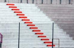 Étapes rouges dans des grandins de stade de football Images libres de droits