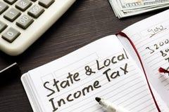 État et impôt sur le revenu local écrits dans la note photographie stock