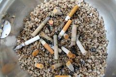 Éteignez-vous les cigarettes sur des pierres image stock