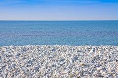 Étendue du gravier blanc sur la côte avec la mer calme sur le backgr photographie stock libre de droits