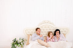 Éternuement été fatigué ou malade de jeune famille dans le lit à la maison Image libre de droits