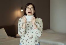 Éternuement asiatique de femme parce que pollution dans la chambre à coucher, jeune allergie obtenue femelle de nez photographie stock libre de droits