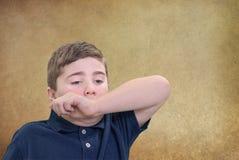 Éternuement de bâche de garçon avec son bras photo libre de droits