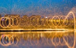 Étincelles d'or chaudes volant de la laine en acier brûlante de rotation de l'homme Photographie stock libre de droits