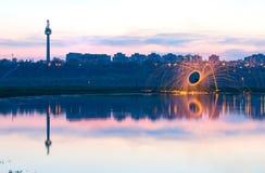 Étincelles d'or chaudes volant de la laine en acier brûlante de rotation de l'homme près de la rivière avec la réflexion de l'eau Photo libre de droits