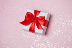 Étincelles rouges d'arc et de scintillement de boîte-cadeau 6èmes sur le fond rose Concept de jour du ` s de St Valentine Photos stock