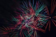 Étincelles rouges, roses, vertes et bleues des feux d'artifice dans le ciel Images stock