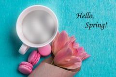Étiquetez bonjour le ressort, les tulipes roses, la tasse de café et les macarons roses Photo stock