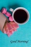 Étiquetez bonjour, les tulipes roses, la tasse de café et les macarons roses Photos stock