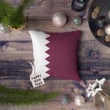 ?tiquette de bonne ann?e avec le drapeau du Qatar sur l'oreiller Concept de d?coration de No?l sur la table en bois avec de beaux images libres de droits