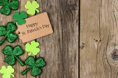 Étiquette de jour de St Patricks avec la frontière de côté de shramrock au-dessus du bois image stock