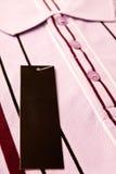 Étiquette de la chemise des hommes neufs Photographie stock