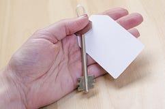 Étiquette de livre blanc attachée à la clé d'argent en métal à disposition Image stock